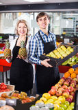 Sellers posing with fruits. Smiling sellers posing with fruits in local marketplace royalty free stock photography