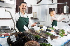 Sellers working in fish store. Middle age seller and assistant offering fresh fish in fish store Stock Photography