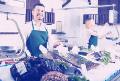 Sellers working in fish store. Middle age seller and assistant offering fresh fish in fish store Royalty Free Stock Photography