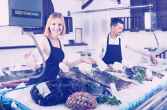Sellers working in fish store stock image