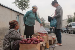 Selling apples in the streets. Two women selling apples in the streets of Osh, Kyrgyzstan. Organic, pesticide free apples in a remote  and undeveloped corner of Stock Image