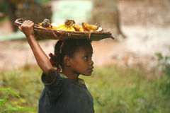 Selling bananas in the rain. Small malagasy girl selling bananas in the rain Stock Photo