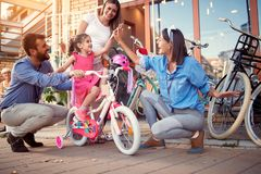 Selling bicycle - Young family buy new bicycle for little girl in bike shop. Selling bicycle - Young family buy new bicycle for happy little girl in bike shop stock image