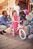 Selling bicycle - Young family buying new bicycle for little girl in bike shop. Selling bicycle - Young family buying new bicycle for happy little girl in bike stock photo