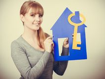 Enjoyable estate agent with house ang key. Selling and buying real estate concept. Young blonde smiling positive female estate agent ready to sell house home Royalty Free Stock Photo