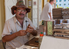Selling Cigars. This gentleman has been rolling custom cigars for over 38 years in Roatan, Honduras. He uses premium Honduran tobacco and makes each cigar with Stock Photos
