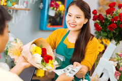 Selling flowers. Woman selling flowers to a man Stock Image
