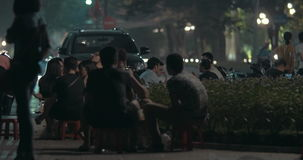 Selling food in the street of Hanoi, Vietnam. HANOI, VIETNAM - OCTOBER 27, 2015: Woman vendor selling food in roadside cafe. Young people sitting at small tables stock footage
