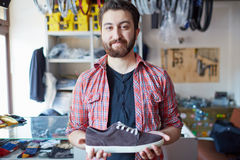 Selling footwear. Portrait of a handsome man selling footwear in sports shop Stock Images