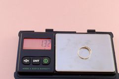 Selling Gold Scrap. A set of digital scales weighs a gold ring that is going to be sold for scrap stock photo