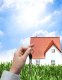 Selling house. On a green field Stock Photography