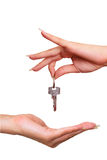 Selling house - giving away key - isolated. Woman hand is giving key when selling home - isolated on white Stock Images