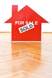 Selling houses concept. With a sold sign on the floor indoors Stock Image