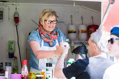 Selling ice cream. RONNEBY, SWEDEN - JUNE 06, 2014: National day of Sweden. Woman selling ice cream to male customer royalty free stock photos