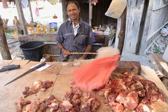 Selling meat on Timor, Indonesia. A butcher selling meat on an everyday regional market in Kefamenanu, West Timor in Indonesia. A man constantly waves a plastic stock images