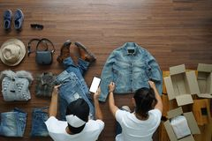 Selling online ideas concept small business owner. Top view men using smart phone and women working shirts and jeans fashion from home on wooden floor with royalty free stock photography