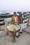 Selling peanuts on the ghats. A vendor of peanuts is standing on the ghats of Varanasi. behind him is the river Ganges with boats Royalty Free Stock Image