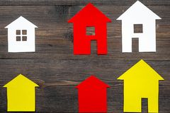 Selling property online with paper house on office desk wooden background top view Stock Photos