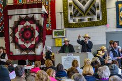 Selling Quilts at Mud Sale. Bart, PA, USA - March 3, 2018: Amish auctioneers sell quilts at the annual Mud Sale at the Bart Fire Company Royalty Free Stock Images