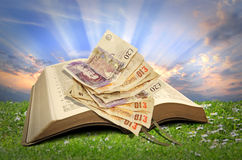 Selling religion. Photo of paper cash resting on open bible depicting selling religion,charity funds,religious organisations etc Royalty Free Stock Photo