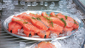 Selling salmon. Fresh salmon fillets on sale at a marketplace, between ice cubes, in Finland Royalty Free Stock Photography