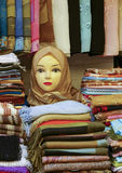 Selling scarves. Colorful scarfs on display on a mannekin head and in piles on a market stall Stock Photo