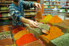Selling spices on grand bazaar. Man scooping spices in a bag for selling, on the grand bazaar, Istanbul, Turkey Royalty Free Stock Image