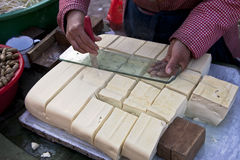 Selling tofu. A Chinese woman was cutting her tofu into pieces for sale at a morning market Royalty Free Stock Images