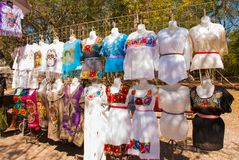 Selling traditional Mexican clothes with floral embroidery and t-shirts with skull painted on the street market in Mexico royalty free stock images