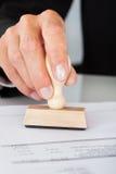 Sello de goma del presionado a mano del hombre de negocios en el documento Fotos de archivo libres de regalías