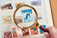 Sello del deporte del franqueo con el esquiador debajo de la lupa en álbum foto de archivo