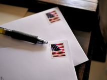 Sellos de la bandera americana en sobres y pluma del correo imagenes de archivo