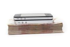2 sellphones кладя на кучу денег наличных денег на белой предпосылке Стоковые Изображения