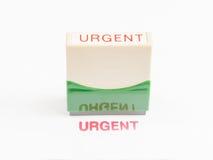 Selo com o urgente na tinta vermelha Fotografia de Stock Royalty Free