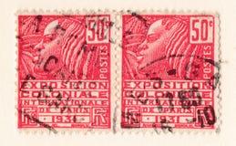 Selo postal francês vermelho velho com uma ilustração de uma mulher africana estilizado que comemora uma exposição colonial em 19 Fotos de Stock