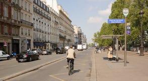 Selon les piétons mobiles de Quai Voltaire, cyclistes et photographie stock libre de droits