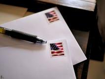 Selos da bandeira americana em envelopes e em pena do correio imagens de stock