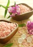 Sels de bain roses en cuvettes et fleurs en bois. Images stock