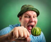 Seltsamer Mann, der sich vorbereitet, Wassermelone zu essen stockfoto