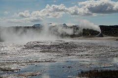 Seltun / Krysuvik Krýsuvík: Fumarole emit sulphur gas behind geothermal field with puddles of hot water stock image