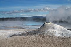 Seltun / Krysuvik Krýsuvík: Mini volcano like fumarole emit sulphuric gas with steaming hot blue natural pool on field stock image
