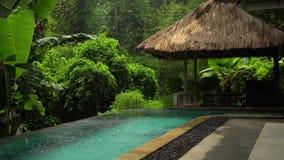 Selva en la lluvia, cámara lenta que tira la piscina al aire libre en el balneario tropical, espacio de la copia almacen de metraje de vídeo