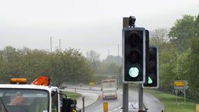 Semáforo del verde del paso de peatones en la ciudad de británicos en día lluvioso cubierto imagenes de archivo
