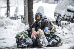 Sem abrigo, vagabundo que senta-se na neve na rua no centro de Sófia, Bulgária Imagens de Stock Royalty Free