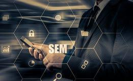 SEM-Suchmaschinen-Marketing Hand des Geschäftsmannholdingbaseballs und -schlaggeräts Lizenzfreie Stockfotos