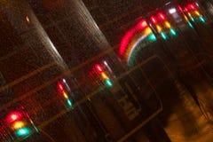 Semafori alla notte riflessa nella tesaurizzazione Immagine Stock