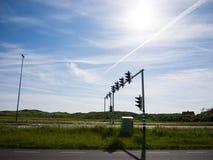 Semafori sulle strade parallele contro un cielo blu Immagini Stock