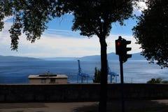 Semaforo pedonale rosso con luce rossa e l'albero con il mare e due gru del porto nei precedenti fotografia stock