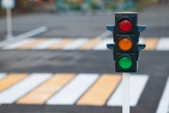 Semaforo sui precedenti della strada e del passaggio pedonale nella città Semaforo rosso, giallo e verde Leggi di traffico, fotografia stock