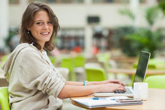 Semale student using laptop at cafeteria table Stock Photos